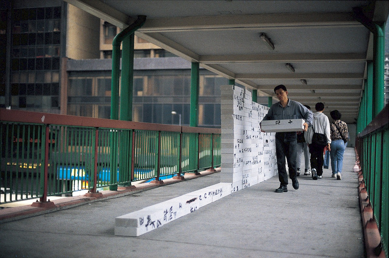 <p>A man carries two white bricks next to a row of similar stacked bricks. The bricks have Chinese characters written on them.</p>